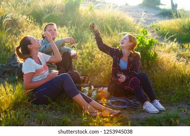 Happy friends having fun outdoors. Young people enjoying time together at countryside during sunset.Fun, joy, leisure concept.