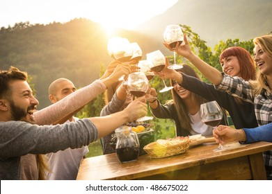 Happy friends having fun outdoors - Young people enjoying harvest time together at farmhouse vineyard countryside - Youth and friendship concept - Hands toasting red wine glass at winery during sunset