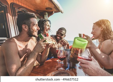 Happy friends having fun outdoors toasting sangria and eating watermelon - Young cheerful people enjoying boat party together in sailing trip - Youth and friendship concept - Focus on left man's eye