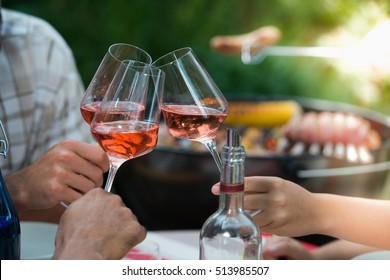 Happy friends having fun outdoors, Focus on hands toasting rose wine glass during barbecue