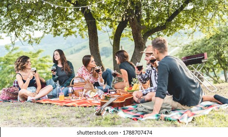 Happy friends having fun at picnic dinner with vintage lights outdoor next vineyard - Young people cheering with red wine on weekend summer day - Friendship, party concept - Focus on left girls faces