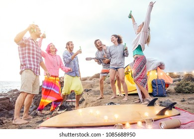 Happy friends having fun playing guitar and dancing on the beach - Group of young people making party drinking beers while camping with tent - Travel, vacation and youth holidays lifestyle concept