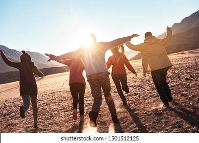 Happy friends having fun and runs at sunset. Togetherness or freedom concept
