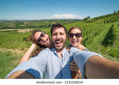 Happy friends having fun taking selfie in winery vineyard - Friendship concept with young people enjoying harvest together at farmhouse - Red wine tasting tour, man with two girls happy in the photo