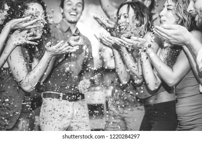 Happy friends having fun throwing confetti at vintage cocktail bar party - Young people hanging out on weekend holiday fest - Youth, friendship and millennials rends concept - Focus on right girl face