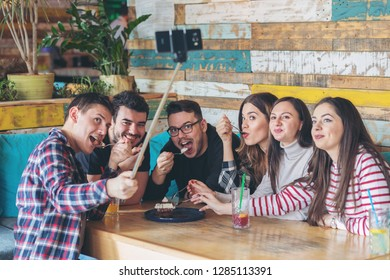 Happy friends having fun together taking selfie at cafe with selfie stick sharing online. Young people addicted by sharing stories on social network community- Millennials lifestyle friendship concept