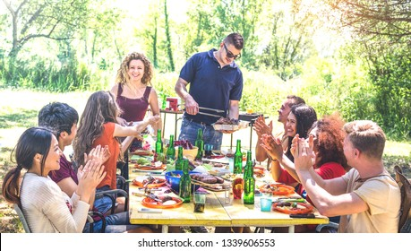 Happy friends having fun together at barbecue picnic party - Young people millenials at pic nic on open air festival - Youth friendship concept with guys and girls eating at barbeque - Warm filter