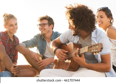 Happy friends having fun together while guy playing guitar. Group of young women and men enjoying their summer vacation. Cheerful young man playing guitar and his friends singing at sunset.