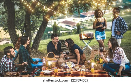 Happy friends having fun at vineyard after sunset - Young people millennial camping at open air picnic under bulb lights - Youth friendship concept with guys and girls drinking wine at barbecue party