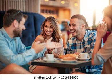 Fröhliche Freunde, die eine tolle Zeit im Café verbracht haben. Freunde sitzen in einem Café, trinken Kaffee und amüsieren sich miteinander.