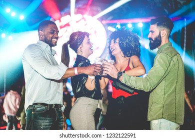 Happy friends having party and drinking beer and cocktails in night club - Young people having fun dancing with laser lights in background - Youth and nightlife concept - Focus on black man hand
