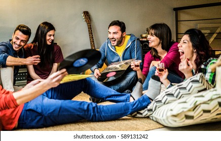 Happy friends having party listening vintage vinyl disc albums at home - Young people having fun drinking shots and laughing together - Warm contrast filter