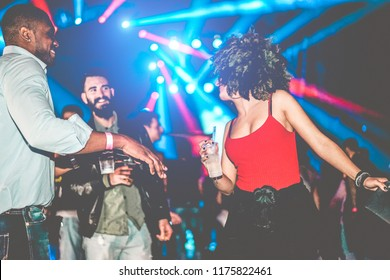 Happy friends having party in night club - Young people having fun dancing inside a trendy club with laser lights in background - Youth and nightlife concept - Focus on woman hand glass