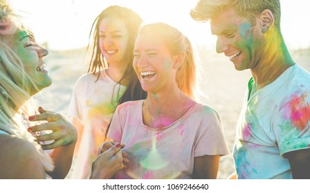 Happy friends having party with powder colors at holi fest - Young people having fun together at beach festival - Youth lifestyle, vacation, summer and friendship concept - Focus on right man face