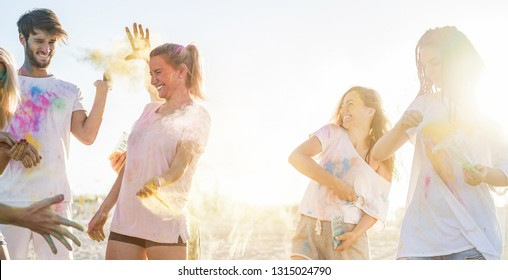 Happy friends having party with powder colors  - Young people having fun together at holi festival - Youth, vacation, summer lifestyle and friendship concept - Main focus on left blond girl face