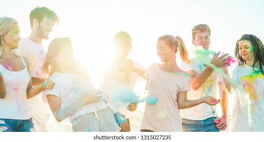 Happy friends having party with powder colors  - Young people having fun together at holi festival - Youth, vacation, summer lifestyle and friendship concept - Main focus on right blond girl face