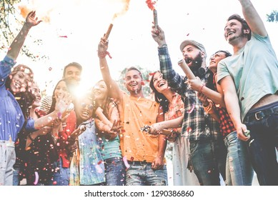 Happy friends having party, throwing confetti and using smoke bombs colors outdoor - Young millennial people celebrating carnival together - Youth concept - Main focus on center guys faces