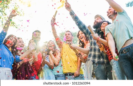 Happy friends having party,throwing confetti and using smoke bombs colors outdoor - Young students laughing and celebrating together - Youth concept - Main focus on three right guys faces