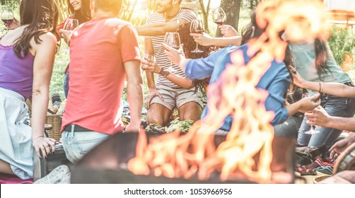 Happy friends having picnic dinner with barbecue in nature outdoor - Young people eating bbq meal and toasting wine - Focus on behind left guys - Youth lifestyle, summer and friendship concept