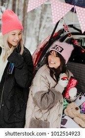 Happy friends having rest in the back of a car while traveling in winter forest