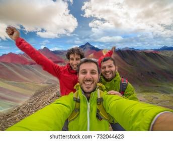 Freudenwanderer fotografieren in Vinicunca, Peru mit Hintergrund des Regenbogenberges (5200 m) in Anden, Cordillera de los Andes, Cusco Region in Südamerika mit bewölktem Himmel