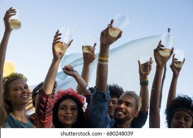 Happy friends holding beer glasses with arms raised while enjoying music festival