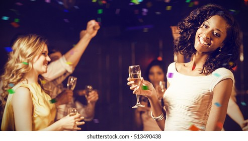 Happy friends holding champagne flute while dancing against flying colours