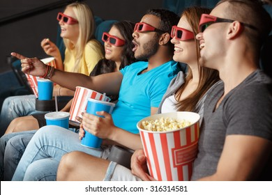 Happy friends holding a refreshment and popcorn in the cinema