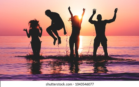 Happy friends jumping inside water on tropical beach at sunset - Group of young people having fun on summer vacation - Youth lifestyle, party and friendship concept - Focus on bodies silhouette