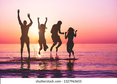 Happy friends jumping inside water on tropical beach at sunset - Group of young people having fun on summer vacation - Youth lifestyle, party and friendship concept - Focus on bodies