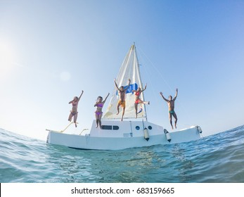 Happy friends jumping off the catamaran boat into the ocean - Young people having fun diving into the sea - Travel, tropical, summer and concept - Soft focus on center guys - Fisheye lens distortion