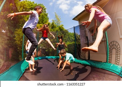 Happy friends jumping on the trampoline in summer