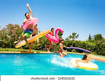 Fröhliche Freunde, die in den Ferien im Pool springen