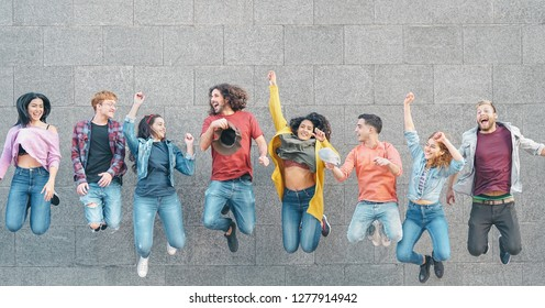 Happy friends jumping together outdoor - Millennial young people having fun celebrating end of school outside - Friendship concept on party celebration and youth lifestyle - Vintage desaturated filter