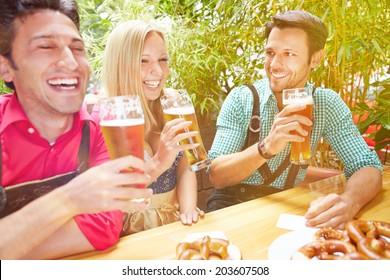 Happy friends laughing in beer garden in Bavaria in summer