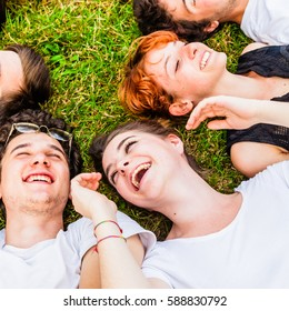 Happy friends laughing and lying on green grass