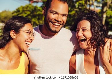 Happy friends laughing in park. Group of cheerful multiethnic friends walking together and laughing in park. Friendship concept