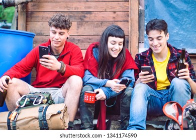 Happy friends looking down at mobile phone - Group of young people using smartphone sitting outdoors on hiking clothing next to wooden wall - Concept of new generations addiction to technology - Image