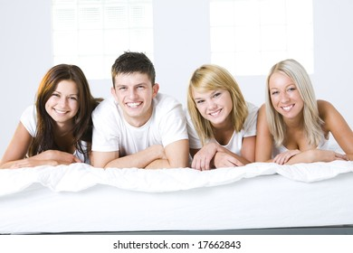 Happy friends lying in bed and looking at camera. Front view.