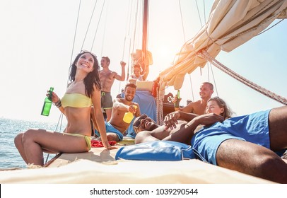Happy friends making boat party with dj playing music at sunset - Young people having fun drinking beers and laughing together in sail sea excursion - Focus on bottom guys - Summer and youth concept