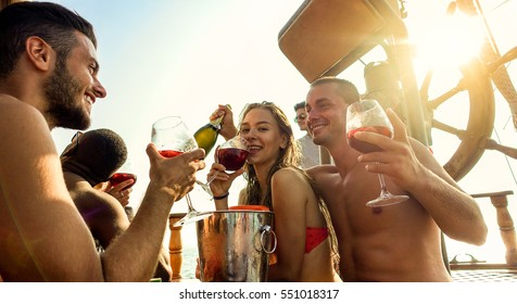 Happy friends making boat party outdoor with sangria and champagne - Young people toasting wine and celebrating summer vacation - Friendship concept - Focus on two right guys - Warm filter