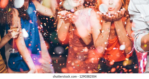 Happy friends making carnival party throwing confetti - Young people celebrating on weekend night - Entertainment, fun, nightlife and fest concept - Focus on center girl hands