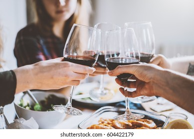 Happy friends making cheers with glasses of red wine, group of people celebrating anniversary at home, cozy atmosphere, family dinning at restaurant, togetherness and traditional concept