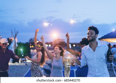 Happy friends making evening beach party outdoor with fireworks and drinking champagne - Young people having fun at chiringuito bar with dj set - Focus on right man face - Youth and summer concept
