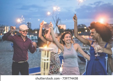 Happy friends making evening beach party outdoor with fireworks - Young people having fun dancing and drinking champagne - Soft focus on center woman hand - Vacation and nightlife concept
