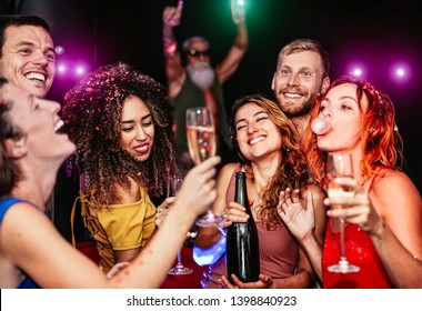 Happy friends making party drinking champagne in the nightclub - Young people having fun celebrating and dancing in the disco club - Nightlife, entertainment and youth lifestyle holidays