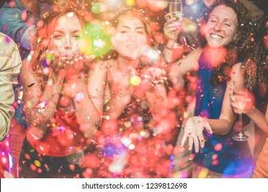 Happy friends making party throwing confetti - Young people celebrating on weekend night - Entertainment, fun, new year's eve, nightlife and fest concept - Focus on left girl face