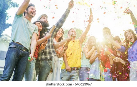 Happy friends making party,throwing confetti and using colorful smoke bombs at party outdoor - Young people having fun together - Soft focus on left girl and bearded man faces - Warm contrast filter