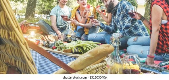 Happy friends making picnic dinner on city park outdoor - Young trendy people drinking wine and laughing outside - Focus on guys faces - Youth, food, summer lifestyle and friendship concept