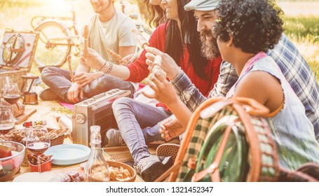 Happy friends making picnic dinner on city park outdoor - Young trendy people drinking wine and laughing outside - Focus on center woman mouth - Youth, food, summer lifestyle and friendship concept